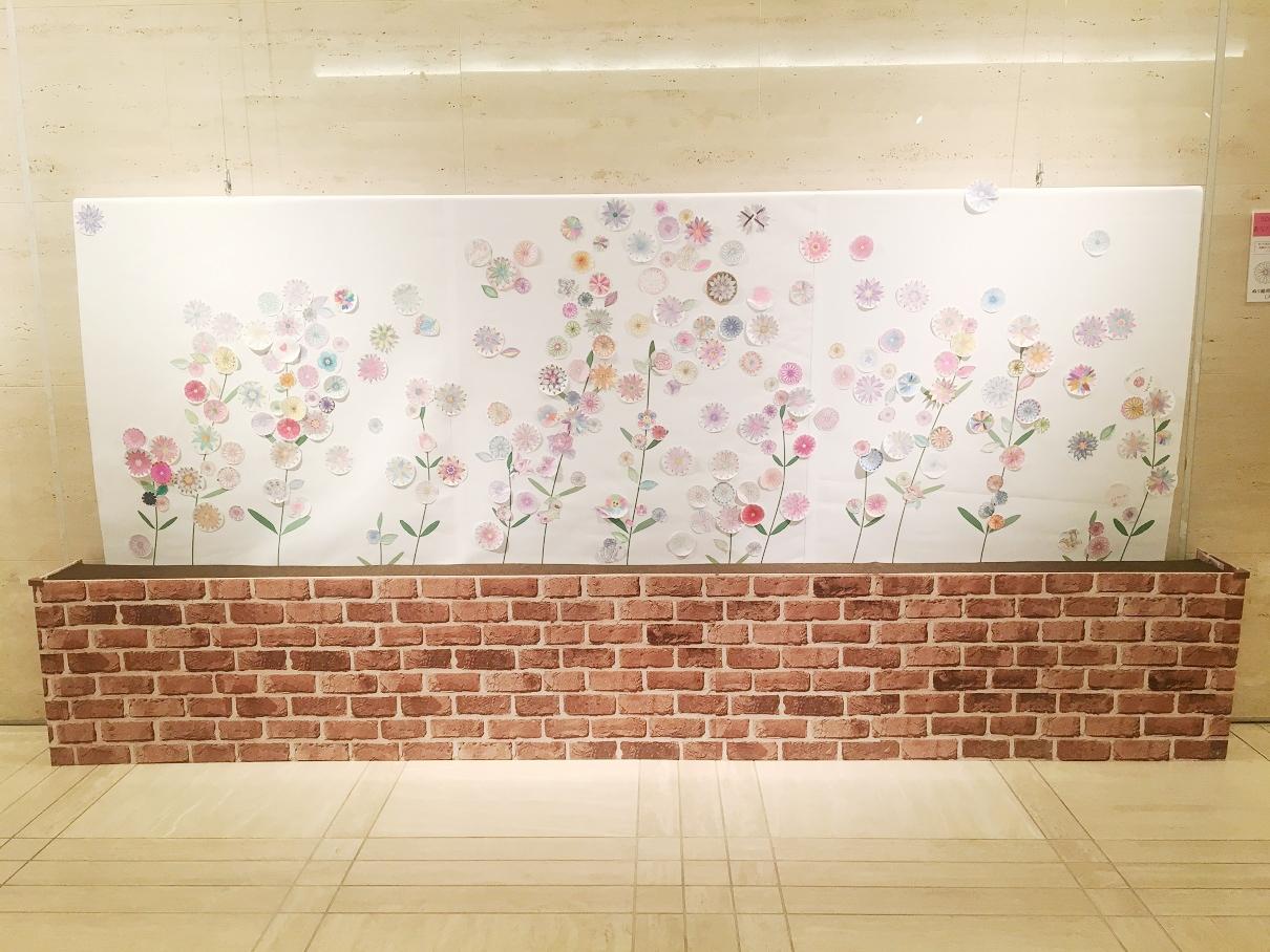 [モードに咲く花展] 開幕1週間! 色えんぴつで彩るフラワー・タペストリーに次々と花が咲いています